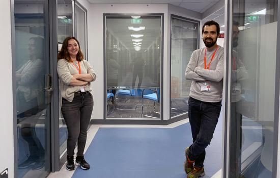 Two Crick researchers, Miguel and Leticia, standing in the corridor in King's College London.