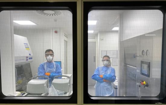 Leticia and Miguel, two Crick researchers in the containment facility at King's College London.