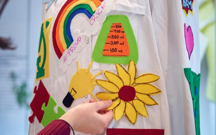 A lab coat with decorations about stereotypes of scientists made by visitors to the 2019 Crick Late.