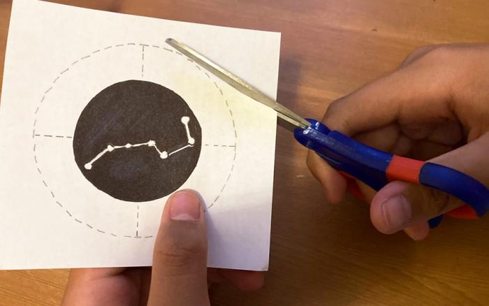 Hands cutting out a constellation design.